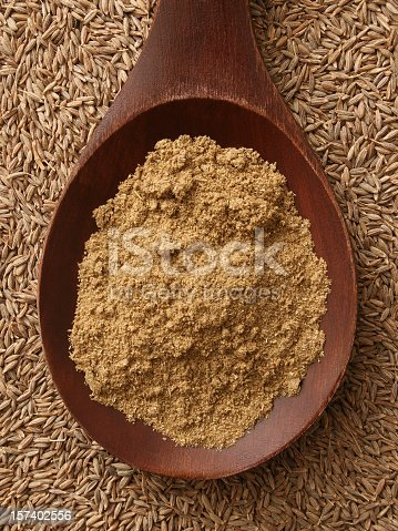 Top view of wooden spoon with ground cumin on it