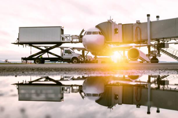 Bodenabfertigung eines weißen Passagierflugzeugs in der Nähe der Boarding Bridge in der Morgensonne. Verladung von Bord-Catering von einem LKW in ein Flugzeug – Foto