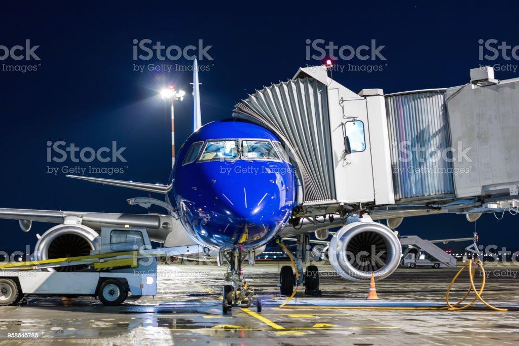 Ground handling of airplane near a passenger ramp at night стоковое фото