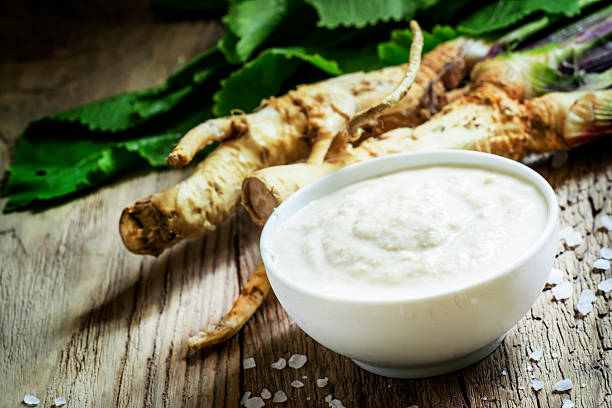 Ground horseradish Ground horseradish, hot sauce to the food in a white bowl, roots and leaves of fresh horseradish, vintage wooden background, selective focus horseradish stock pictures, royalty-free photos & images