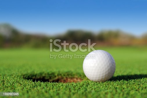 istock Ground level close up of golf ball close to hole 155392045