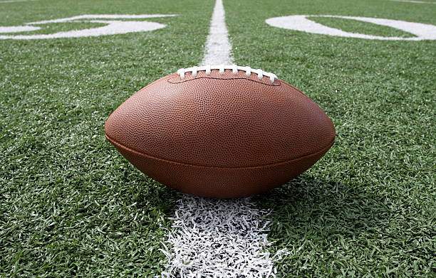 Ground level view of a football on the fifty yard line Football centered and near the fifty yardline turf stock pictures, royalty-free photos & images