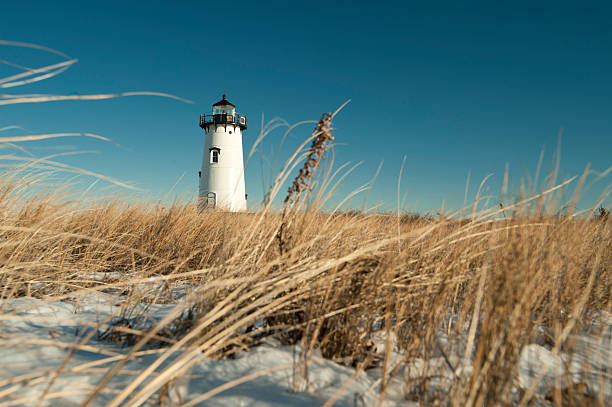 Ground level view of a lighthouse in Edgartown Cape Cod LIghthouse with dried grass and snow in the foreground cape cod stock pictures, royalty-free photos & images
