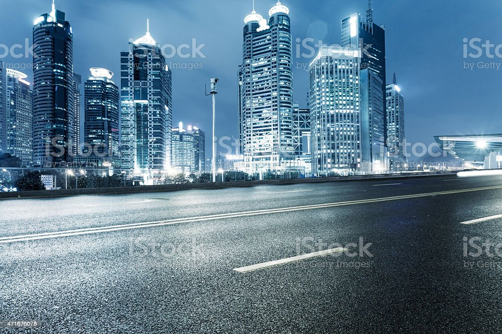 Ground level view of an urban road and illuminated skyline stock photo