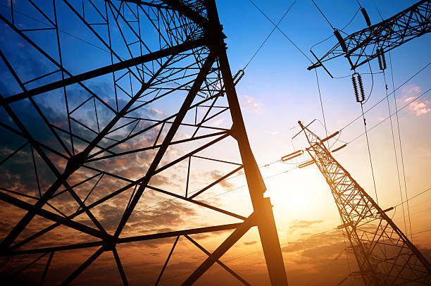 ground level view of high-voltage pylons - transmission lines stock photos and pictures