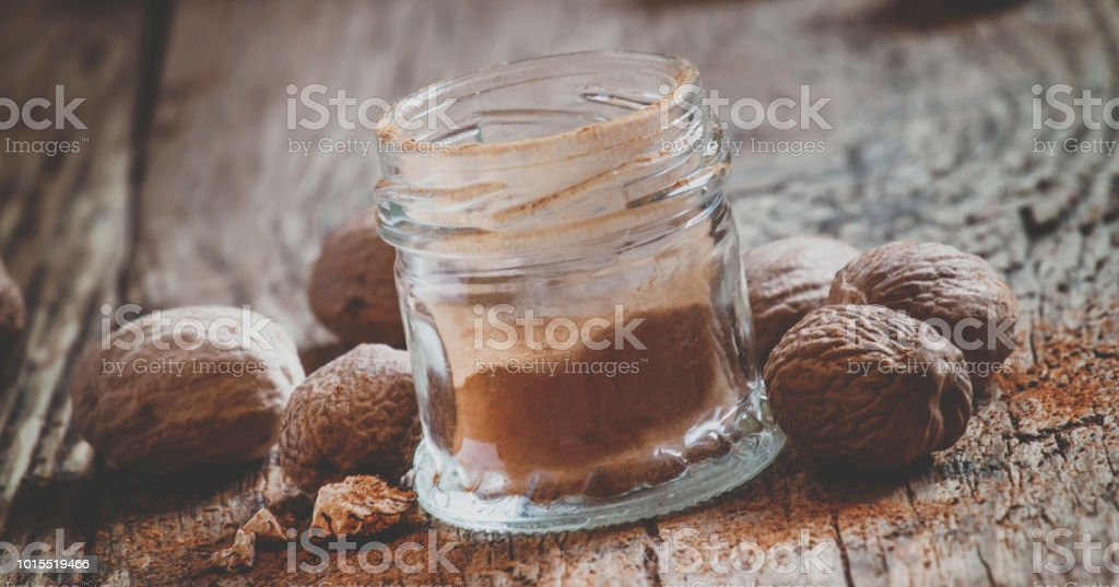 Ground nutmeg in a jar and whole nuts on an old wooden background, selective focus and toned image stock photo