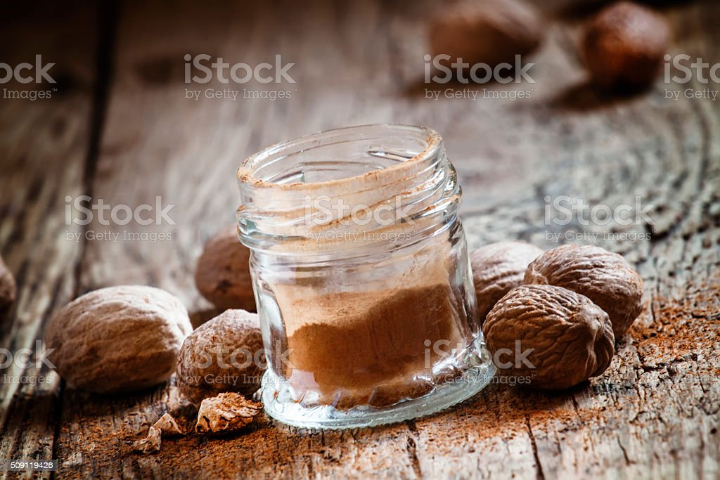 Ground nutmeg in a jar and whole nuts stock photo