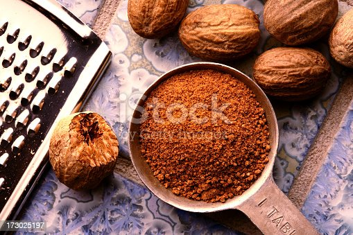 Ground nutmeg in measuring spoon, with un-ground nuts and grater on patterned blue tile ground.