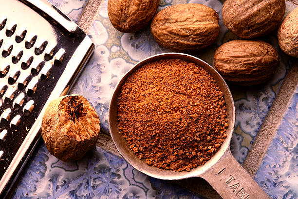 Ground nutmeg in measuring spoon Ground nutmeg in measuring spoon, with un-ground nuts and grater on patterned blue tile ground. nutmeg stock pictures, royalty-free photos & images