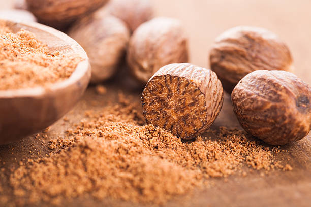 Ground nutmeg Ground nutmeg spice in the wooden spoon closeup nutmeg stock pictures, royalty-free photos & images