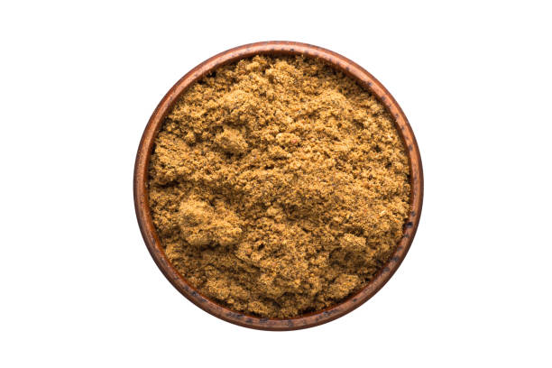 ground nutmeg powder spice in wooden bowl, isolated on white background. Seasoning top view ground nutmeg powder seasoning in a wooden bowl, top view. spice isolated on white nutmeg stock pictures, royalty-free photos & images