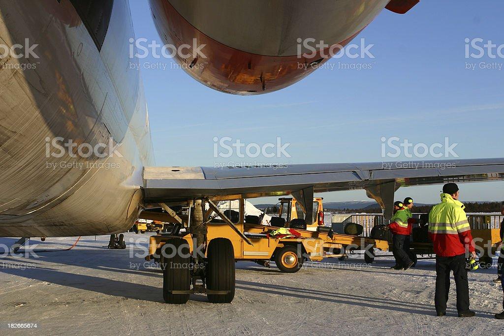ground staff loading luggage onto aeroplane Kiruna airport Sweden winter royalty-free stock photo