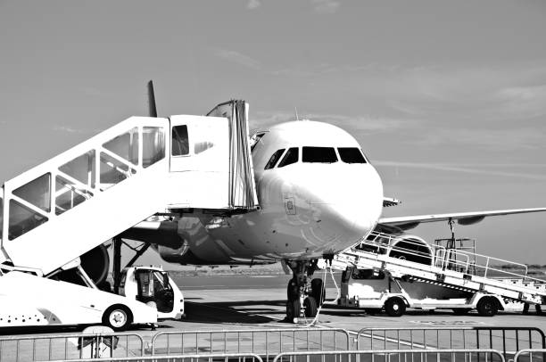 Ground Support Equipment And Vehicles Attend To Air Airplane. Black And White stock photo