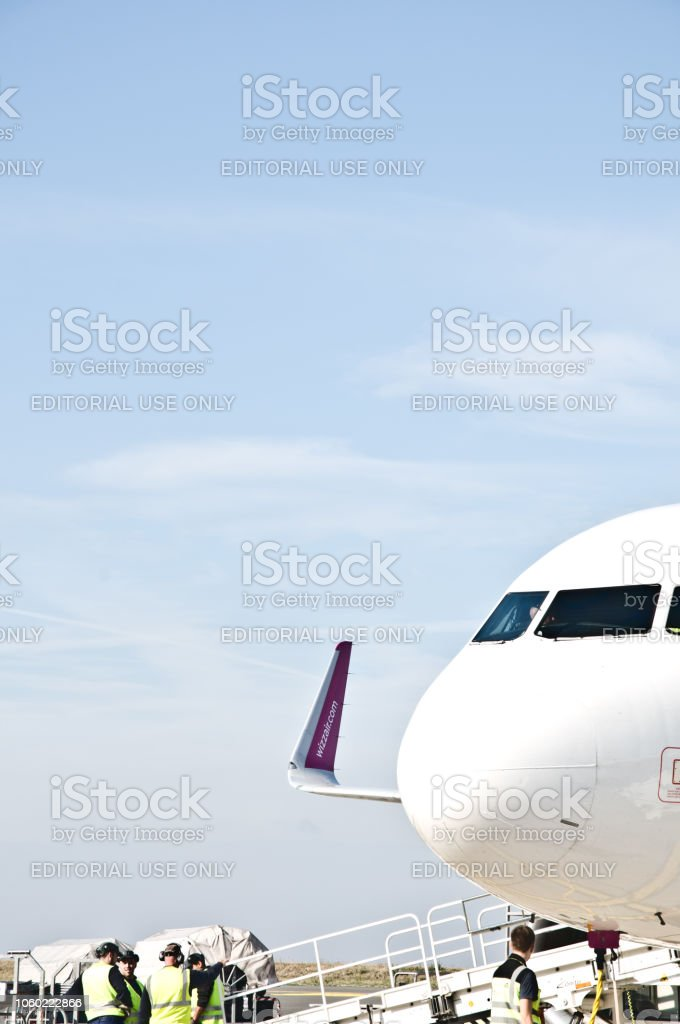Ground Support Staff And Vehicles Attend To Hungarian Wizz Air Airplane At Dortmund International Airport aka Flughafen Dortmund (IATA: DTM, ICAO: EDLW), Germany stock photo