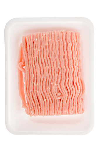 An overhead close up of 99% lean ground turkey meat laying on a white styrofoam tray.  You can substitute ground  turkey for  ground beef  in any recipe. Isolated on white.