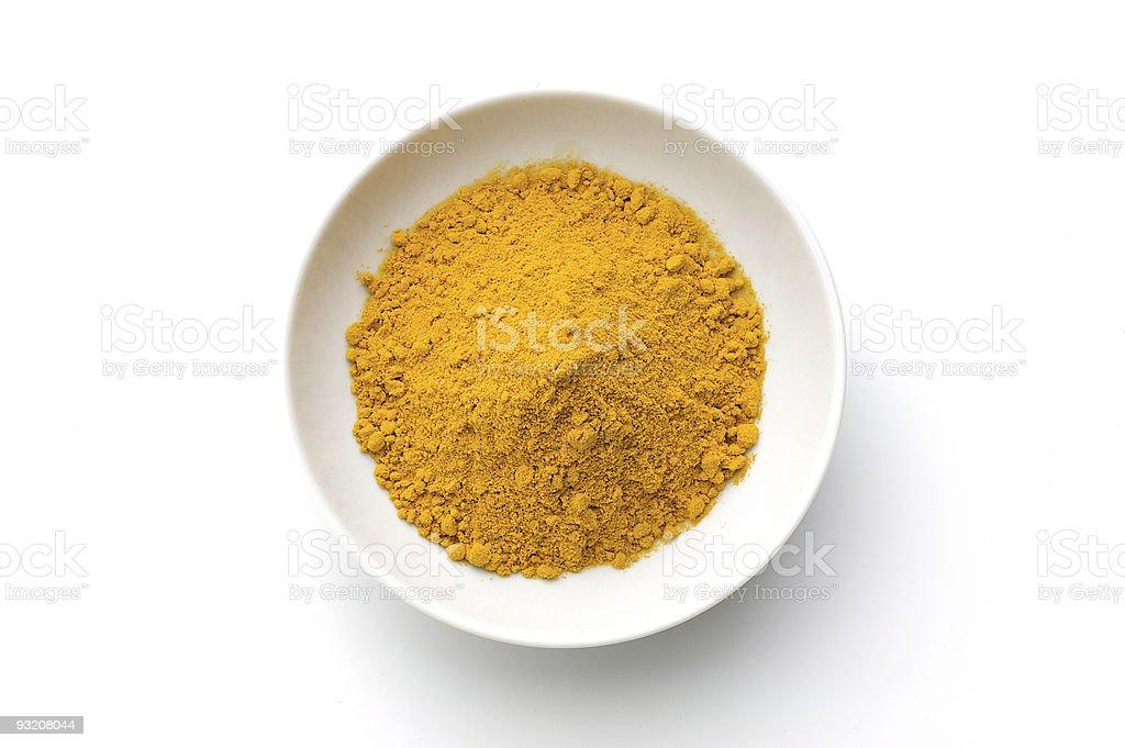 Ground turmeric powder in a white bowl on a white background stock photo