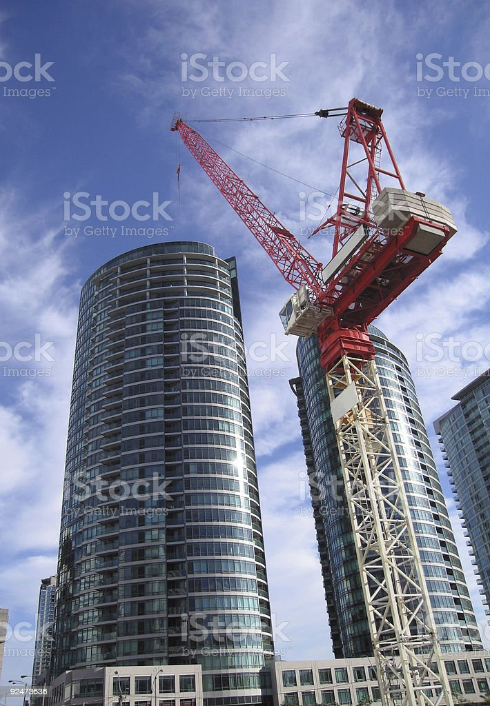 A ground view of a crane working on skyscrapers royalty-free stock photo