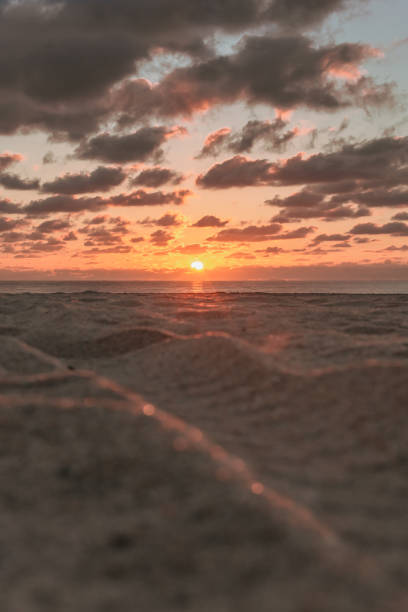 Ground view of a sandy beach at sunrise stock photo