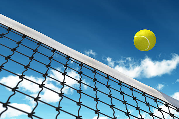 Ground view of a tennis ball coming over a net with blue sky stock photo