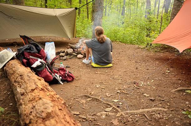 ground view of girl sitting by campfire in hiking campsite - planenzelt stock-fotos und bilder