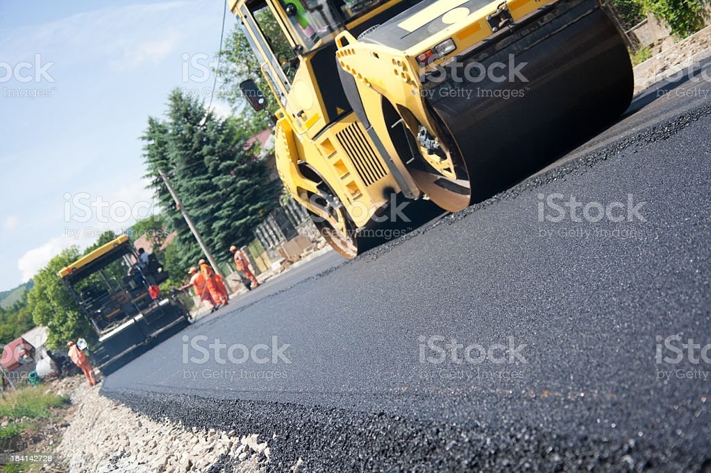 Ground view of machines paving asphalt stock photo