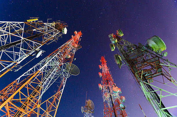 Ground view of telecommunication towers Telecommunication mast with microwave link and TV transmitter antennas in night sky . long exposure about 2-3 minutes telecommunications equipment stock pictures, royalty-free photos & images