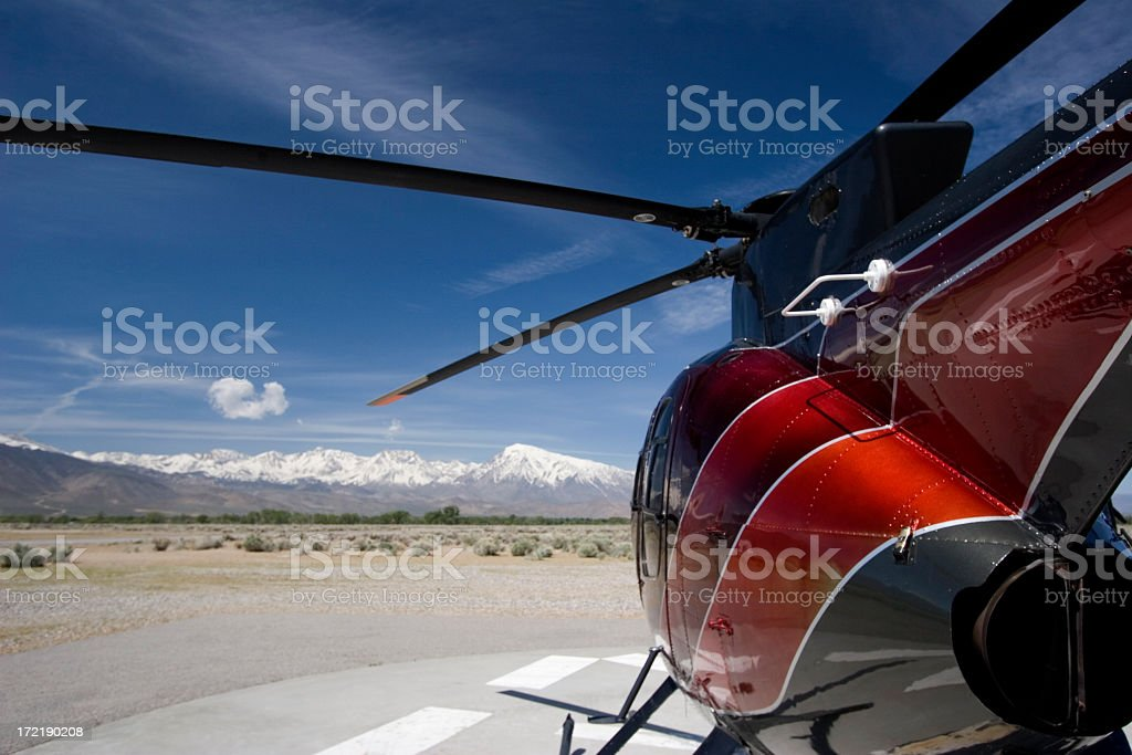 Grounded red Hughes helicopter in the desert on a clear day royalty-free stock photo