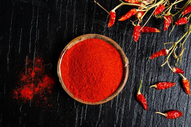 geaarde rode paprika in een kom - paprikapoeder stockfoto's en -beelden