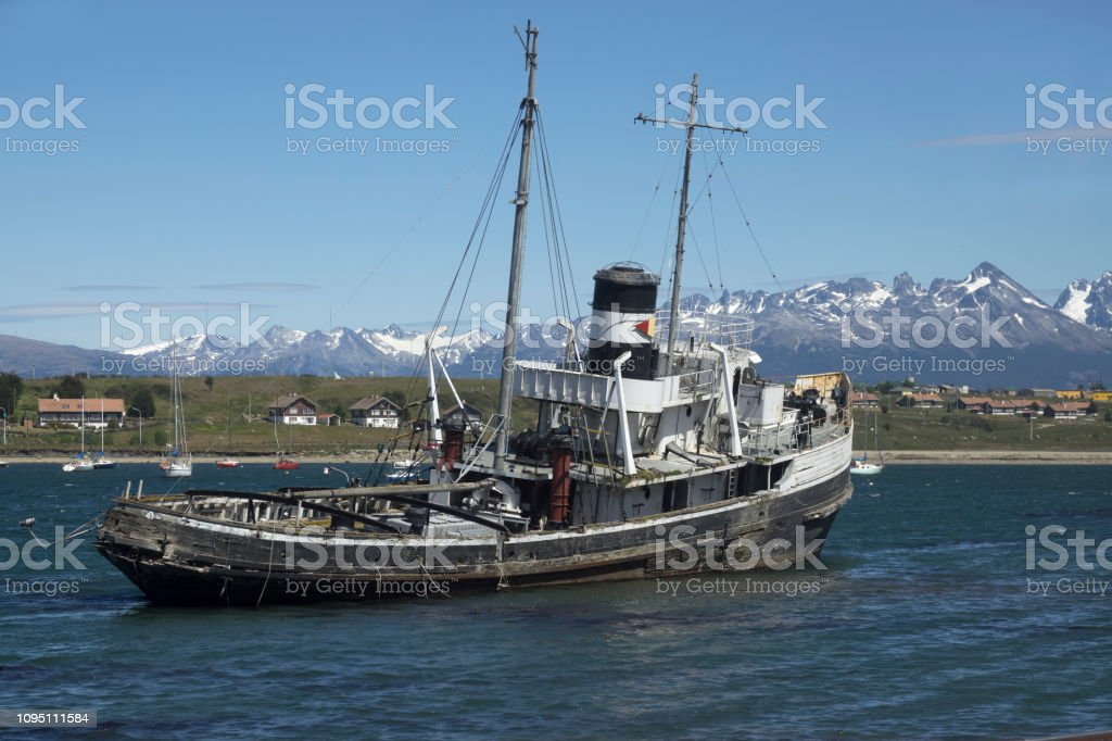 Grounded tugboat shipwreck Ushuaia Argentina Montes Sampaio mountains Chile stock photo