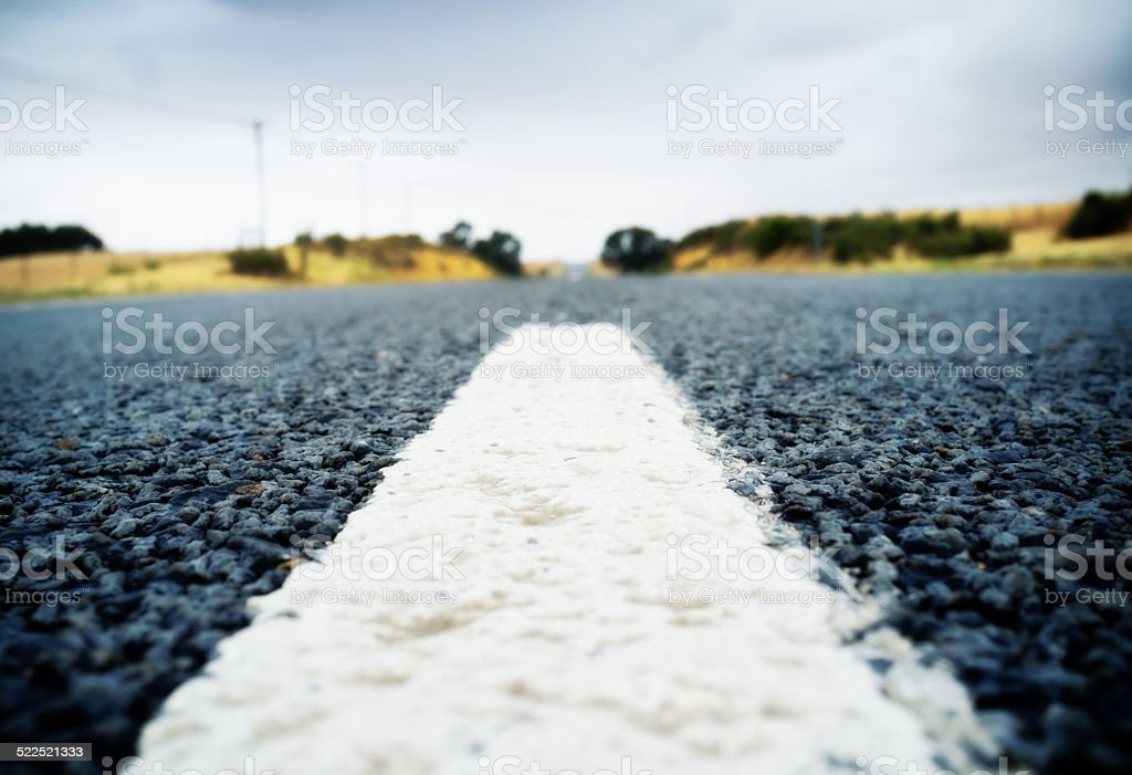 Ground-level view of country road unrolling into distance stock photo