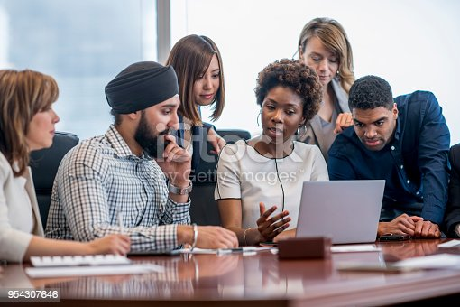 A diverse group of business people gather around a laptop in a modern office and discuss what they see.