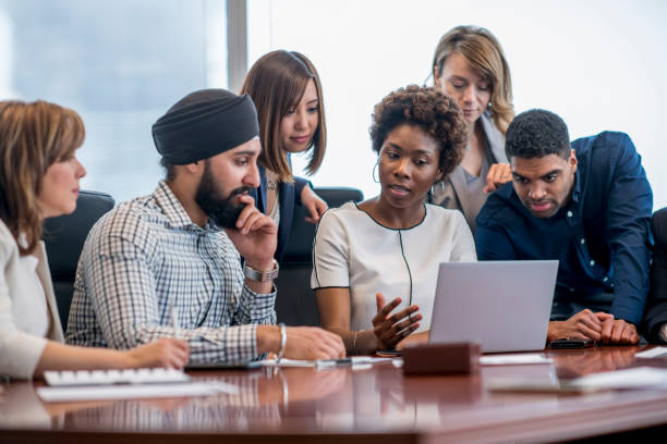 Group analysis of digital data A diverse group of business people gather around a laptop in a modern office and discuss what they see. multi ethnic group stock pictures, royalty-free photos & images