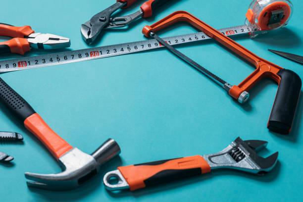 Gruppe Bündel von Werkzeugen mit orangen Griffen auf blauem Hintergrund schließen – Foto