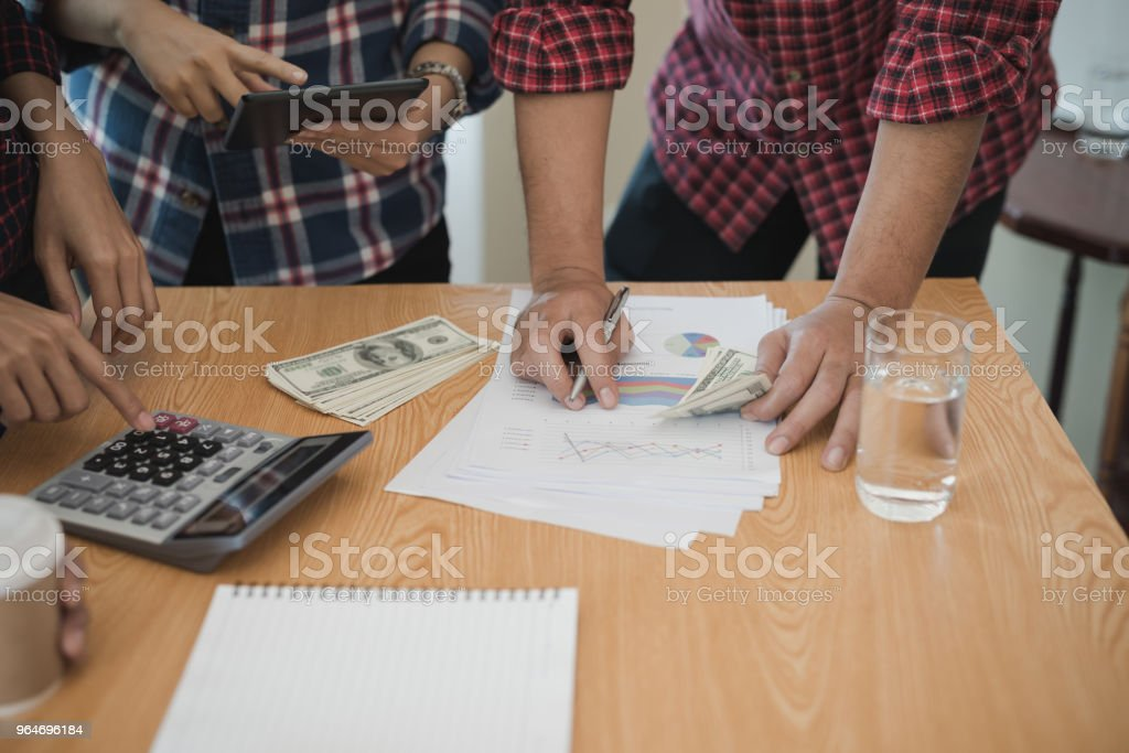Group business man and woman use calculator. She is calculated the share of business royalty-free stock photo
