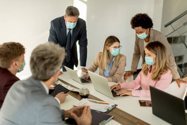 Group business people have a meeting and working in office and wear masks as protection from corona virus stock photo