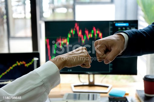 group businessman fist bump hand at the office table between computer laptop , success or agreement about their job.