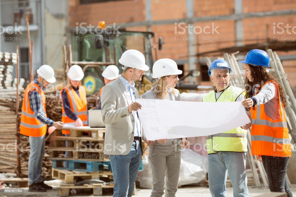 Group Construction workers looking at blueprints on construction site стоковое фото
