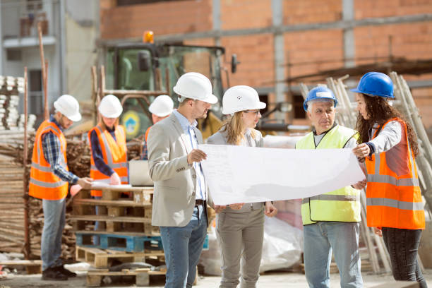 Group Construction workers looking at blueprints on construction site stock photo