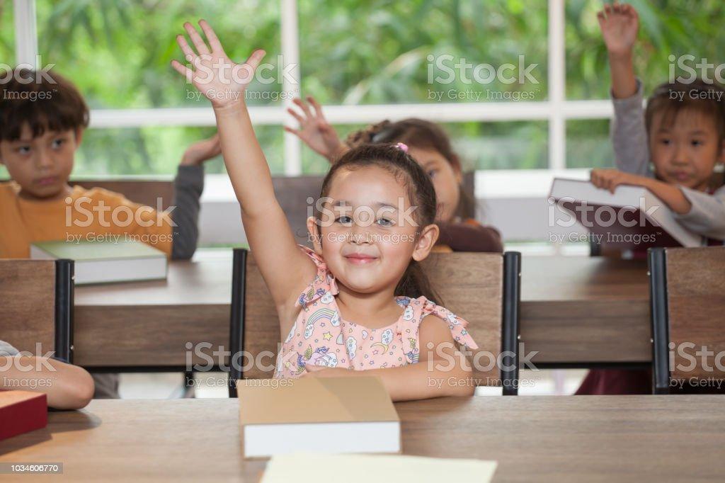 Schattig klein meisje student verhogen handen in de klas school