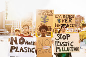 istock Group demonstrators protesting against plastic pollution and climate change - Multiracial people fighting on road holding banners on environments disasters - Global warming concept 1211345433