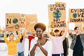istock Group demonstrators protesting against plastic pollution and climate change - Multiracial people fighting on road holding banners on environments disasters - Global warming concept 1214684113