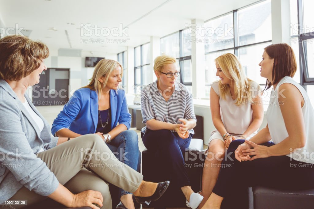 Group discussion in office Team of women discussing during a training session in modern office. Adult Stock Photo