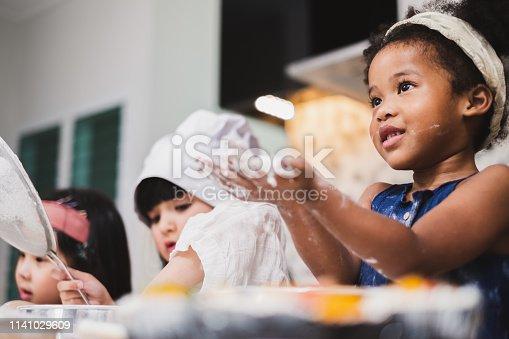istock Group diversity kids girl making cake bakery in kitchen 1141029609