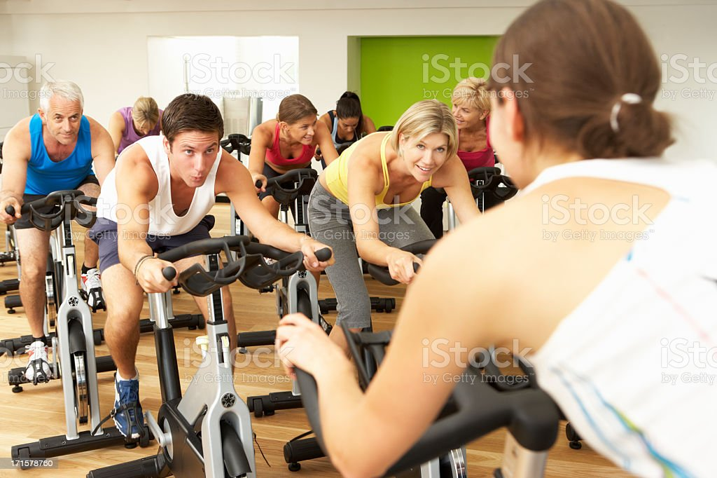 Group Doing Spinning Class In Gym stock photo