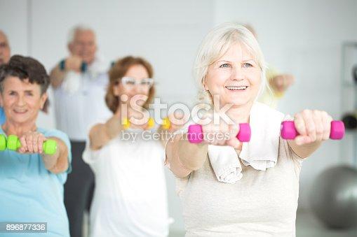 Elderly women holding dumbbells during group exercise class for senior citizens