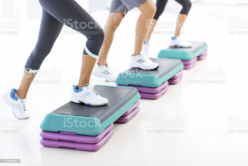 Grupo de exercícios na academia de ginástica com aparelhos de step - foto de acervo