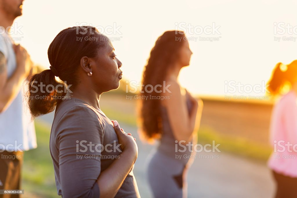 Group exercising Yoga outdoors at sunset stock photo