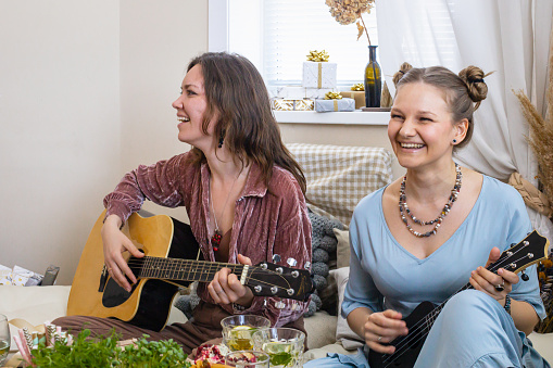 Questa immagine ha l'attributo alt vuoto; il nome del file è group-female-friends-playing-guitar-singing-song-having-fun-at-in-picture-id1317061192