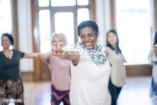 A woman of African descent is indoors in a fitness studio. She is taking a meditation class, and reaching her arms out.