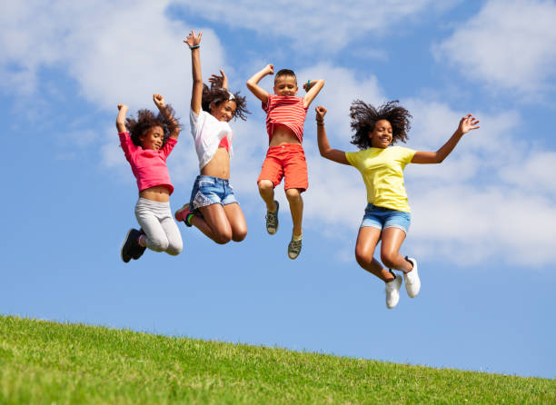 Group four jumping kids over blue sky stock photo